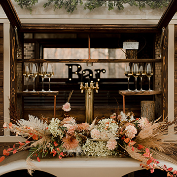 Floral center piece on vintage mobile horse box bar