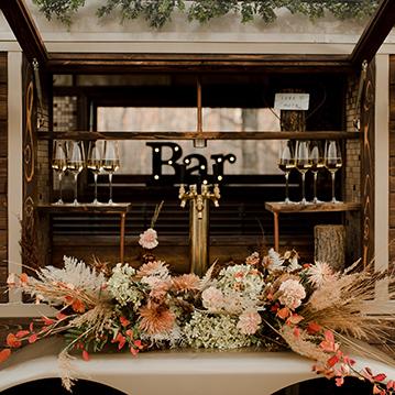 Floral center piece on vintage mobile horse box bar