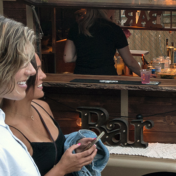 Women smiling being served drinks from a mobile bar