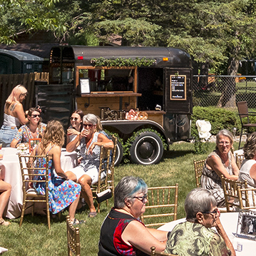 Group of people enjoying drinks outdoors with vintage mobile box bar